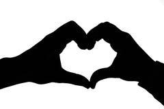 Kobiety i mężczyzna ręki tworzy serce. Sylwetka. Zdjęcia Royalty Free