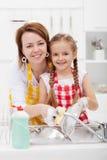 Kobiety i małej dziewczynki domycia naczynia w kuchni fotografia stock