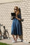 Kobiety i rocznika bicykl i biały ściana z cegieł, zielony gazon Blondynki dziewczyna stoi na zewnątrz biura, trzyma pastylkę Zdjęcia Stock