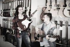 Kobiety i samiec 14-21 lat wybiera między akustyczny Obraz Royalty Free