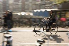 Kobiety Jadą jej rower w Amsterdam ruchu drogowym, holandie obraz royalty free