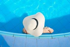 Kobiety jest ubranym słomianych kapelusze i relaksują w pływackim basenie obrazy stock