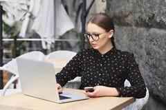 Kobiety jest ubranym szkła, czarna koszula w kawiarni pisać na maszynie coś Obraz Royalty Free