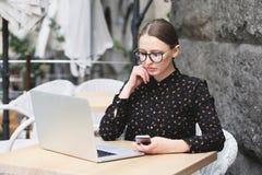 Kobiety jest ubranym szkła, czarna koszula w kawiarni pisać na maszynie coś Obrazy Royalty Free