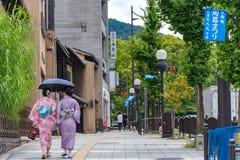 Kobiety jest ubranym tradycyjnego smokingowego kimonowego odprowadzenie na ulicie woko?o tradycyjnych budynk?w w Kyoto zdjęcie stock