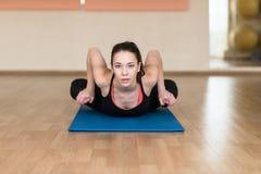 Kobiety joga, Bhekasana, żaby poza w gym obraz stock