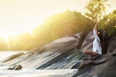 Kobiety joga Medytuje na skale na ocean plaży obrazy royalty free
