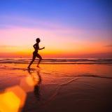 Kobiety jogger na plaży przy zmierzchem Obraz Royalty Free