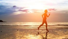 Kobiety jogger przy zmierzchem na seashore Zdjęcia Royalty Free