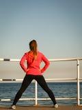Kobiety jogger rozciągliwość na molu nadmorski fotografia royalty free