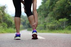 Kobiety jogger trzyma ona sport raniąca noga obrazy stock