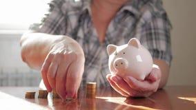 Kobiety kładzenia moneta w prosiątko banku, oszczędzanie pieniądze pojęcie Przyszłość potrzebuje pożyczkową edukację lub hipotecz zbiory wideo