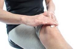 Kobiety kładzenia śmietanka na jej kolanie Fotografia Stock