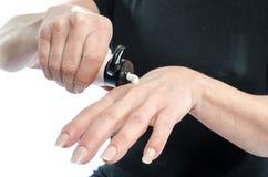 Kobiety kładzenia śmietanka na jej ręce Zdjęcia Stock