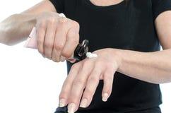 Kobiety kładzenia śmietanka na jej ręce Zdjęcia Royalty Free