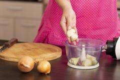 Kobiety kładzenia cebule w cebulkowego siekacz zdjęcie royalty free
