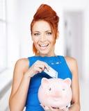 Kobiety kładzenia gotówki pieniądze w prosiątko banka Zdjęcia Royalty Free