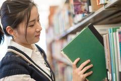Kobiety kładzenia książka z powrotem na półka na książki zdjęcia royalty free