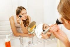 Kobiety kładzenia makeup w prochowym pokoju używać muśnięcie zdjęcie royalty free