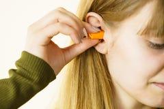 Kobiety kładzenia ucho czopuje w ucho fotografia stock
