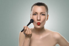 Kobiety kładzenia Makeup na twarzy z Pouting wargami Zdjęcie Royalty Free