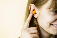 Kobiety kładzenia ucho czopuje w ucho Obrazy Stock