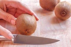 Kobiety karmowy przygotowanie - ciąć kiwi owoc Zdjęcie Royalty Free