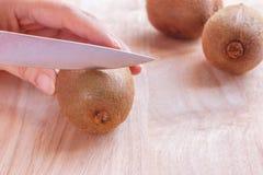 Kobiety karmowy przygotowanie - ciąć kiwi owoc Obrazy Stock
