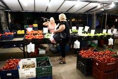 Kobiety klient i sprzedawca stoi blisko stojaka świezi warzywa i owoc zdjęcie stock