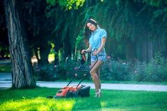 Kobiety kośby gazon w mieszkaniowym tylnym ogródzie Zdjęcia Royalty Free