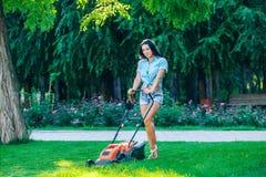 Kobiety kośby gazon w mieszkaniowym tylnym ogródzie dalej Zdjęcia Royalty Free
