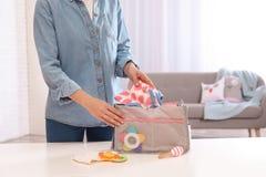 Kobiety kocowania dziecka akcesoria w macierzyńską torbę na stole indoors obrazy stock