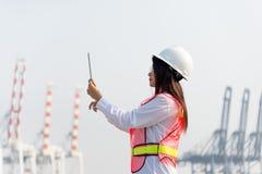 Kobiety konstruują mienia działanie z zbiornika ładunku zafrachtowań statkiem w stoczni i laptop przy półmrokiem dla Logistycznie Fotografia Stock