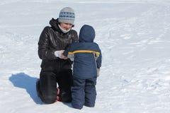 Kobiety korygować odziewa dziecko w śniegu Obraz Stock