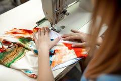 Kobiety krawcowa szy kolorowego płótno w warsztacie zdjęcia stock