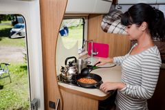 Kobiety kucharstwo w obozowiczu, motorhome RV wnętrze Zdjęcie Stock
