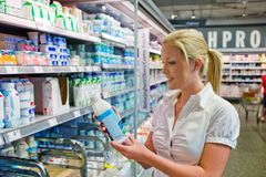 Kobiety kupienia mleko przy sklepem spożywczym Zdjęcie Royalty Free