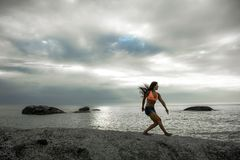 Kobiety lądowanie na skale przy zmierzchem na Bakovern plaży, Kapsztad fotografia royalty free
