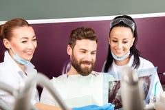 Kobiety lekarka i jej uśmiechnięty pomocniczy pokazuje zębu promieniowanie rentgenowskie Obraz Royalty Free