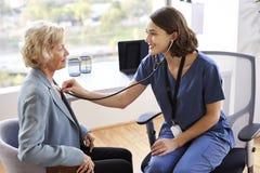 Kobiety lekarka Jest ubranym pętaczki W Biurowym słuchaniu Starsza Żeńska pacjent klatka piersiowa Używać stetoskop obraz royalty free