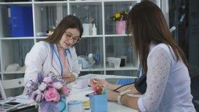 Kobiety lekarka mierzy naciska pacjent w biurze przy kliniką i pisze jej przydziale zbiory wideo