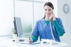 Kobiety lekarka przy recepcyjnym biurkiem obraz stock