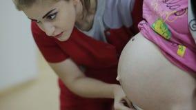 Kobiety lekarka słucha podbrzusze kobieta w ciąży stetoskopem zdjęcie wideo