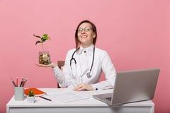 Kobiety lekarka siedzi przy biurko prac? na komputerze z medycznymi dokumentu chwyta monetami w szpitalu odizolowywaj?cym na past zdjęcie royalty free