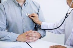 Kobiety lekarka sprawdza kierowego rytm pacjent i poleca fundę obrazy stock