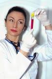 Kobiety lekarka sprawdza reakcję w próbnej tubce Zdjęcie Royalty Free