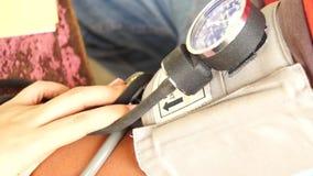 Kobiety lekarka używa aneroidu sphygmomanometer ciśnienia krwi wymiernika brać cierpliwego ` s ciśnienie krwi zdjęcie wideo