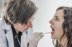 Kobiety lekarka używa jęzoru depressor z dziewczyna pacjentem obraz royalty free