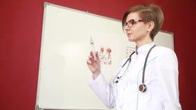 Kobiety lekarka w lab żakiecie z stetoskopem pokazuje strzykawkę zbiory wideo