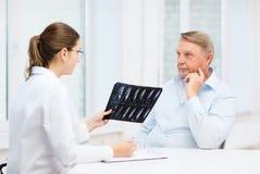 Kobiety lekarka z starym człowiekiem patrzeje promieniowanie rentgenowskie zdjęcie stock
